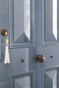 grey wooden door with yellow key on a key ring